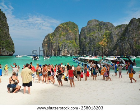 MAYA BAY, THAILAND - FEBRUARY, 2015: Crowds of visitors enjoy a day trip at Maya Bay, one of the iconic beaches of  Phi Phi  islands of Southern Thailand. - stock photo