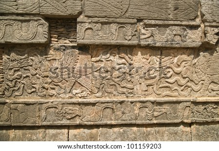 Mayan figures carved into wall at Chichen Itza in Mexico - stock photo