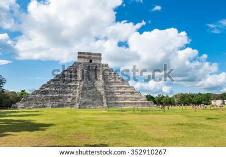 Mayan pyramid Chichen Itza on the green grass with cloudy sky in Mexico - stock photo