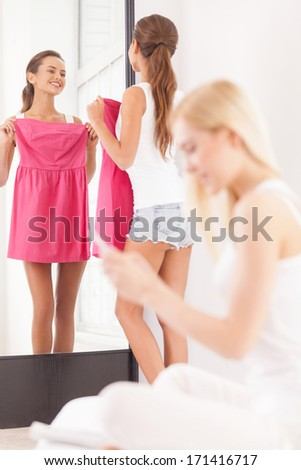 Maybe this dress? Beautiful young woman holding dress and looking at the mirror while another women sitting on the foreground and looking at the mobile phone - stock photo