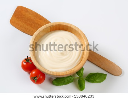 mayonnaise in with tomatoes, in a wooden bowl with kitchen wooden spoon - stock photo