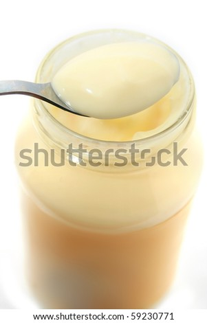 Mayonnaise on spoon isolated on white - stock photo