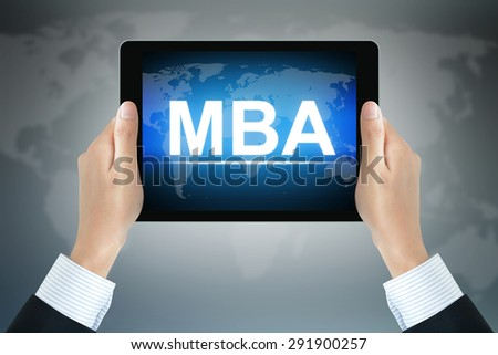 MBA sign on tablet pc screen held by businessman hands - online MBA concept - stock photo