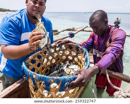 MBUDYA ISLAND, TANZANIA: MARCH 08, 2015: Two fishermen in modern clothes with a traditional boat on Mbudya Island, close to Dar es Salaam, Tanzania, East Africa, on a sunny day. One man holds a fish. - stock photo