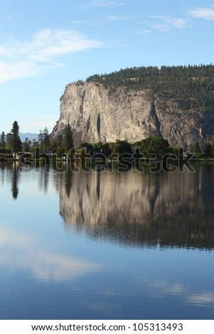 McIntyre Bluffs and Vaseux Lake, Okanagan, BC, vertical. The calm water of Vaseux Lake mirror the McIntyre Bluffs in the Okanagan Valley, British Columbia, Canada. - stock photo