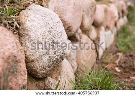 meadow divided by an old stone wall, which used to be a border - stock photo