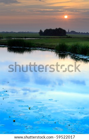 Meadow with canal and waterlilies at sunrise, the Netherlands - stock photo