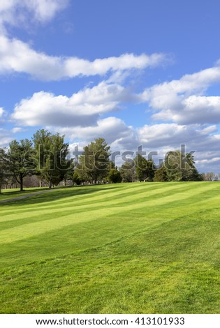 Meadow with green spring grass.Green field and blue sky. Spring background. Open golf course field. Puffy clouds with trees and green field - stock photo