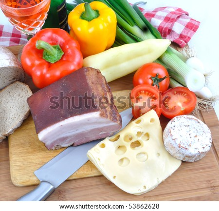 Meal concept with bread, onion, tomatoes, cheese, wine, bacon and pepper. - stock photo