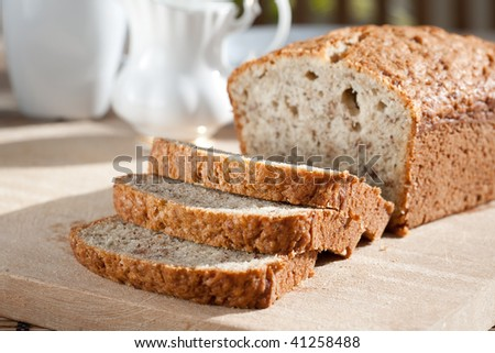 Meal setting with sliced banana bread and serving bowls. - stock photo