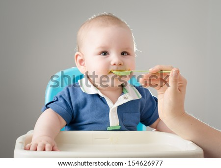 Meal Time. Adorable baby boy eating. The hand of his mother is feeding him with a spoon. High definition image. - stock photo