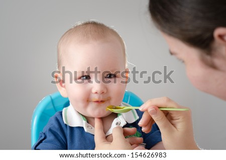 Meal Time. Adorable baby eating. The hand of his mother is feeding him with a spoon. High definition image. - stock photo