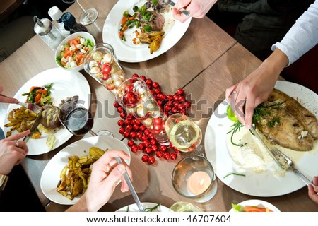 Meals being eaten on a restaurant table decorated for christmas - stock photo