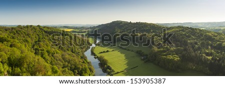 Meandering River Wye making its way through lush green rural farmland in the warm early sunlight. - stock photo