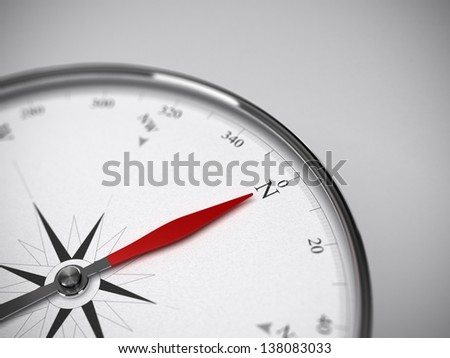 Measure instrument, compass with red needle pointing to the north. Blur effect focus on the letter N. Grey background - stock photo