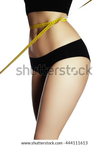 Measure on woman body on white background. Fashion photo of sexy young woman in lingerie with slim body sitting on a diet and measuring the waist with a centimeter tape - stock photo