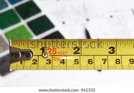 measure tape and architectural plans and materials - stock photo