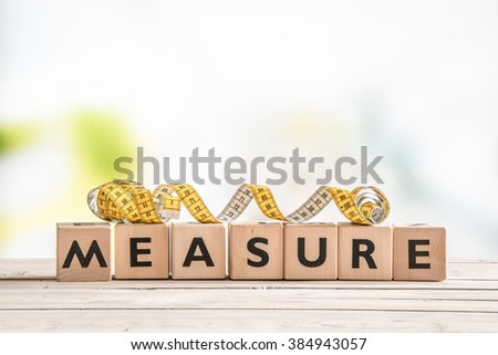 Measure word on a wooden table with measure tape - stock photo