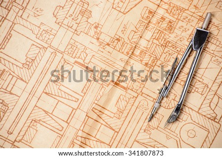 Measuring and drawing instruments and old drawings are on the table - stock photo
