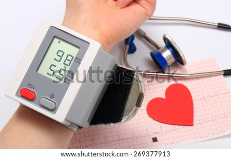 Measuring blood pressure, heart shape and stethoscope on electrocardiogram, medicine concept - stock photo