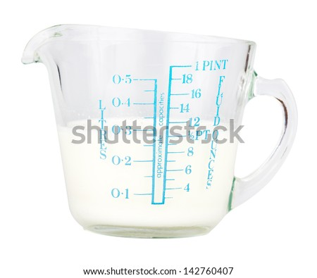 Measuring cup containing milk  isolated on white with clipping path - stock photo