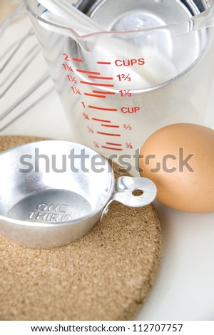 measuring cup with kitchenware and egg - stock photo