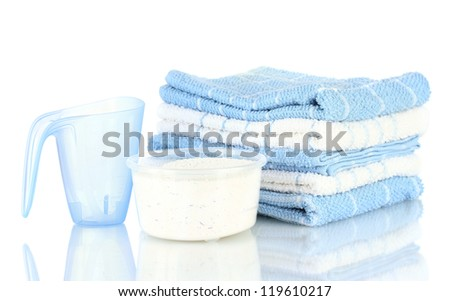 measuring cups with washing powder and towels, isolated on white - stock photo