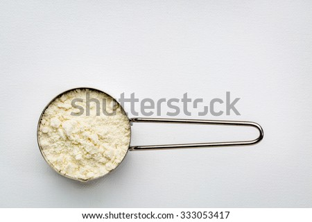 measuring metal scoop of whey protein powder against rustic white art canvas with a copy space - stock photo