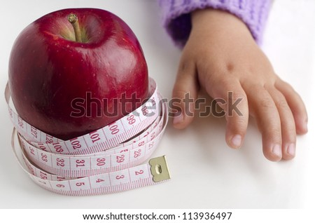 Measuring meter over a diet apple with child hand. - stock photo