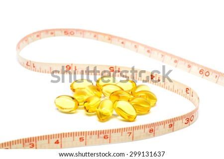 Measuring tape and Omega 3 capsules for dieting concept on white background - stock photo