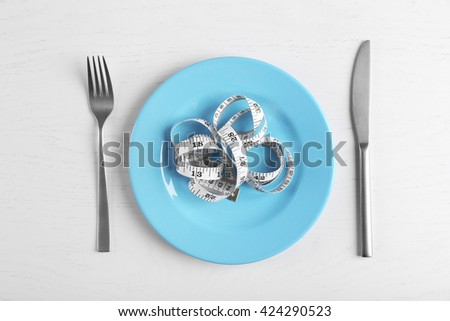 Measuring tape in empty plate on white table.. Top view. - stock photo