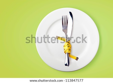 Measuring tape on a fork and knife  - dieting concept image - stock photo