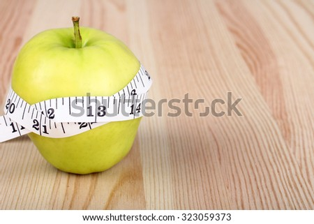 measuring tape on Apple on wooden background - stock photo