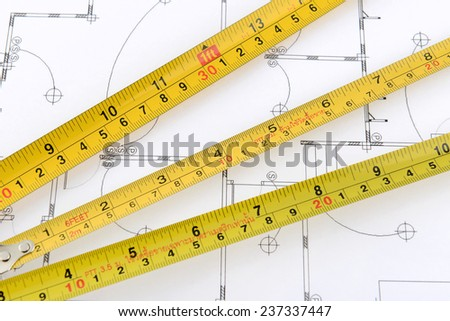 measuring tape on plans - stock photo