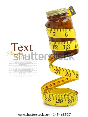 Measuring tape with a bottle of diet pills - stock photo