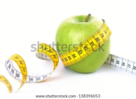 Measuring tape wrapped around a green apple. Diet concept - stock photo