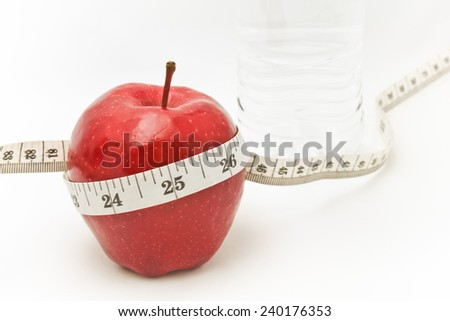 Measuring tape wrapped around a red apple as a symbol of diet. - stock photo