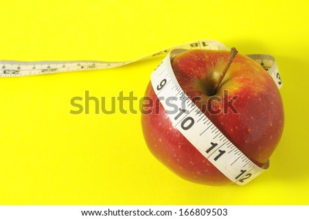 Measuring Tape Wrapped Around a Red Apple as Symbol of Diet - stock photo