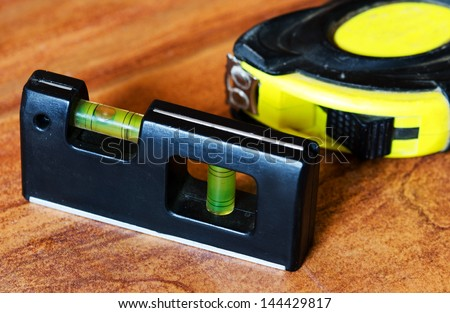 Measuring tools (level spirit and tape measure) on a floor tile. - stock photo