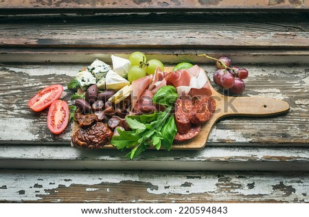 Meat and cheese appetizers selection on a rough painted wood background - stock photo