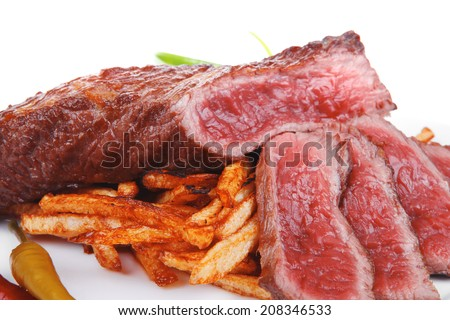 meat and potato : rare grilled beef steak served with pepper and tomato over plate isolated on white background - stock photo