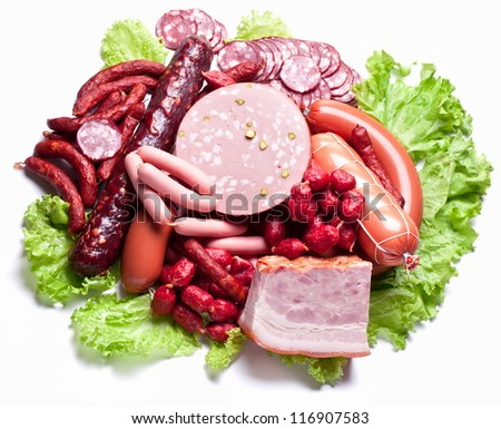 Meat and sausages on lettuce leaves. Isolated on white. - stock photo