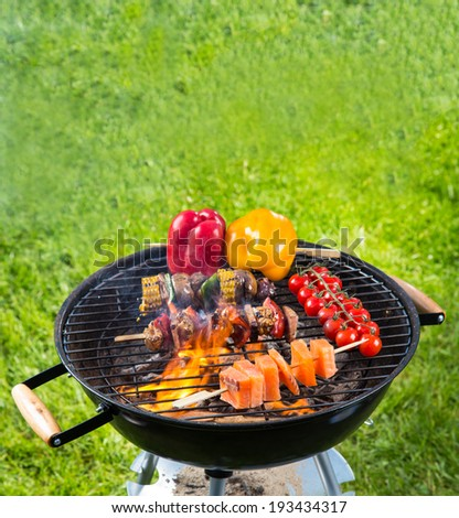 Meat and vegetable on barbecue grill with fire - stock photo
