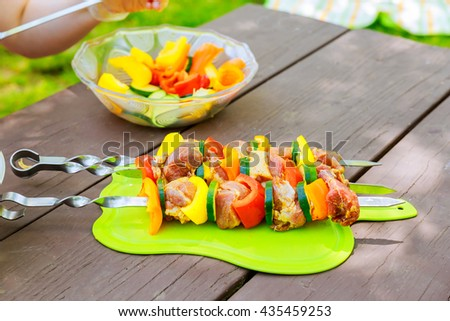 Meat and vegetable skewers on grill in nature - stock photo