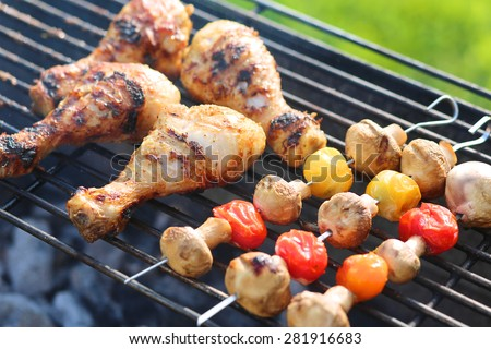 Meat and vegetables on grill. Marinated chicken legs and mushrooms with cherry tomatoes on metal skewers roasted on barbecue grid for summer family dinner - stock photo