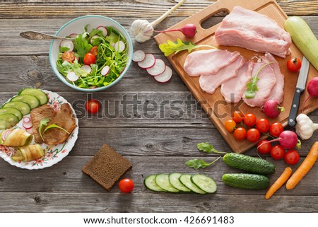 meat and vegetables on old wooden table - stock photo
