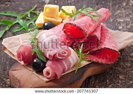 Meat appetizer on a plate on old wooden background - stock photo