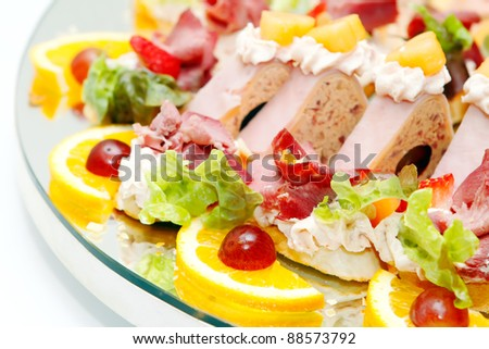 Meat assortment with salad, oranges and grapes, focus on food in the bottom third - stock photo