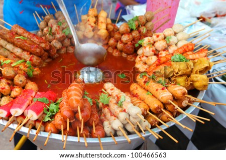 Meat balls and sausages on sticks in a bowl with sauce on Phuket market, Thailand - stock photo
