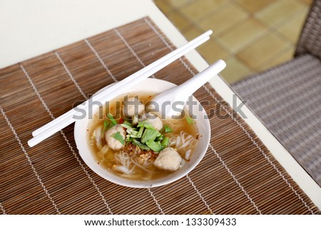 Meat balls noodle in a white bowl with chopsticks - stock photo
